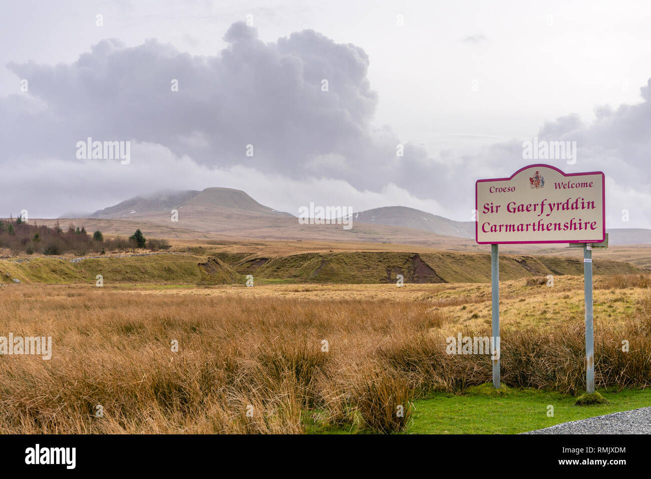 'Welcome to Carmathenshire' sign with cumulonimbus clouds over the Black Mountain range (Carmarthen Fans) in the Brecon Beacons, Wales, UK - Stock Image