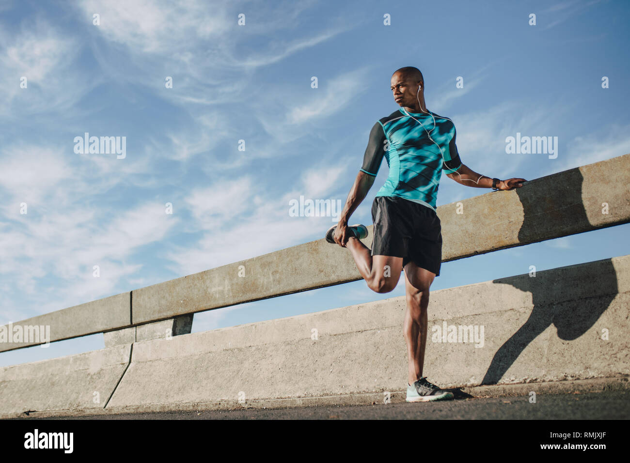 Urban male runner standing by the street and stretching his legs. Young sportsman warming up before a run in morning. - Stock Image