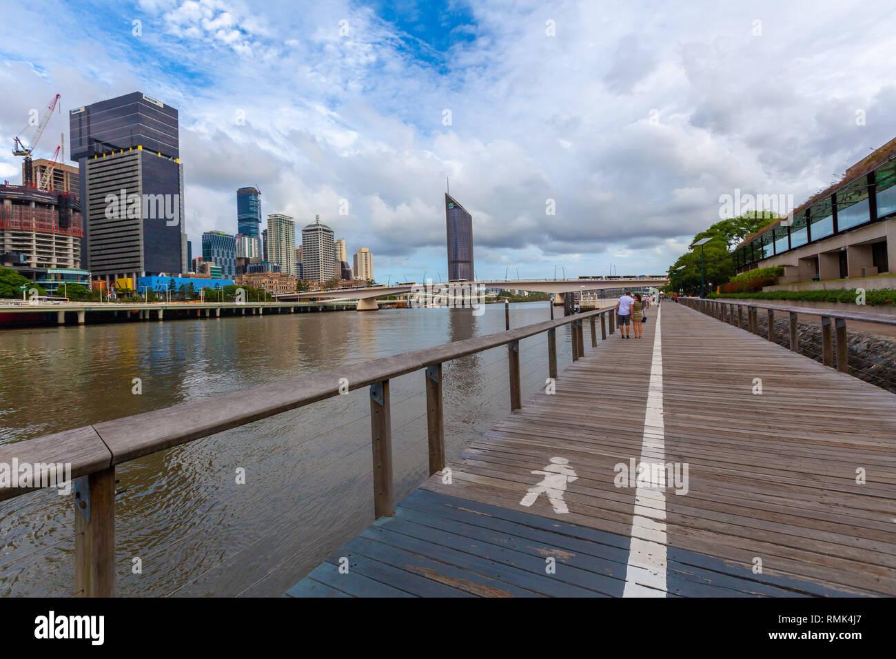 BRISBANE, Australia - January 9 2019: Wooden boardwalk along Brisbane river - Stock Image