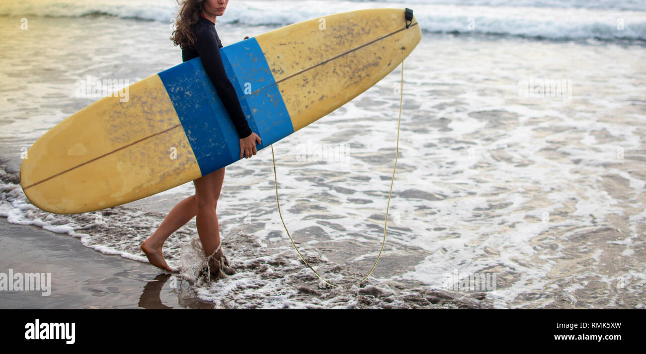young attractive and happy surfer girl in beautiful beach carrying yellow surf board walking in the ocean enjoying summer holidays at tropical island - Stock Image