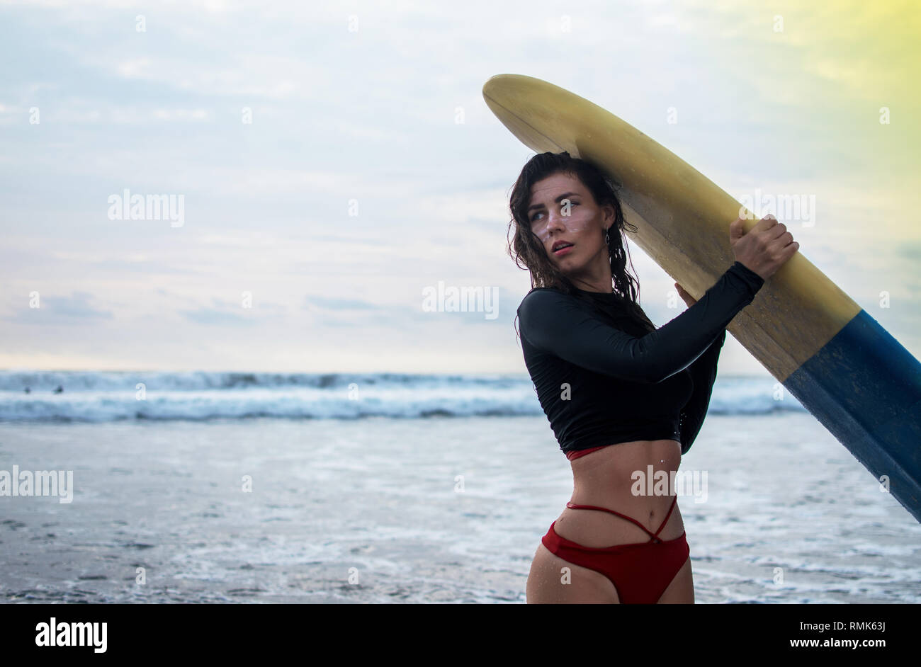 Outdoor shot of young girl waxes surfboard for safe riding waves, dressed in black swimsuit, takes care of safety, with white lines mask on her pretty - Stock Image