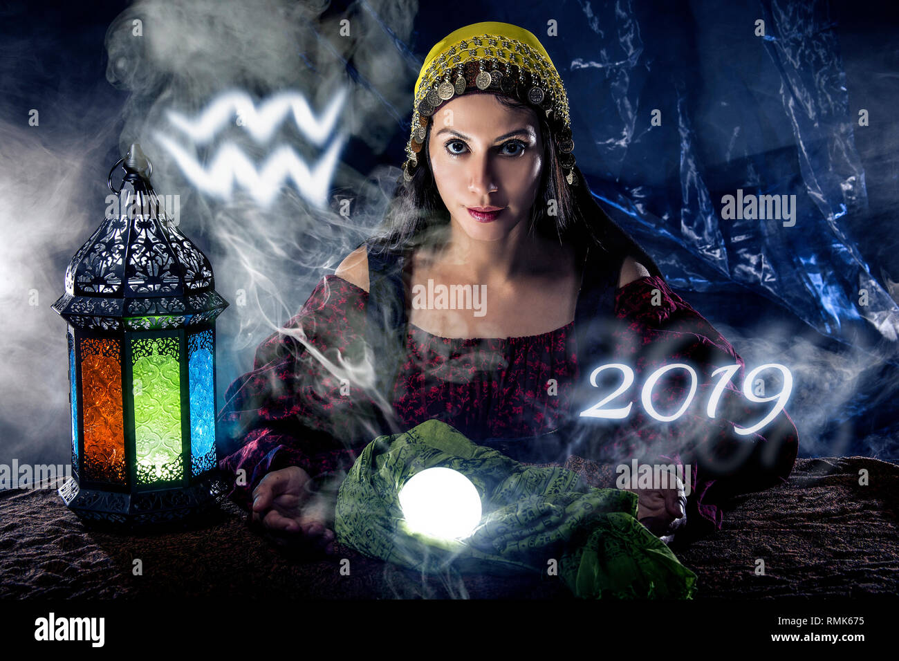 Psychic or fortune teller with crystal ball and horoscope zodiac sign of Aquarius - Stock Image