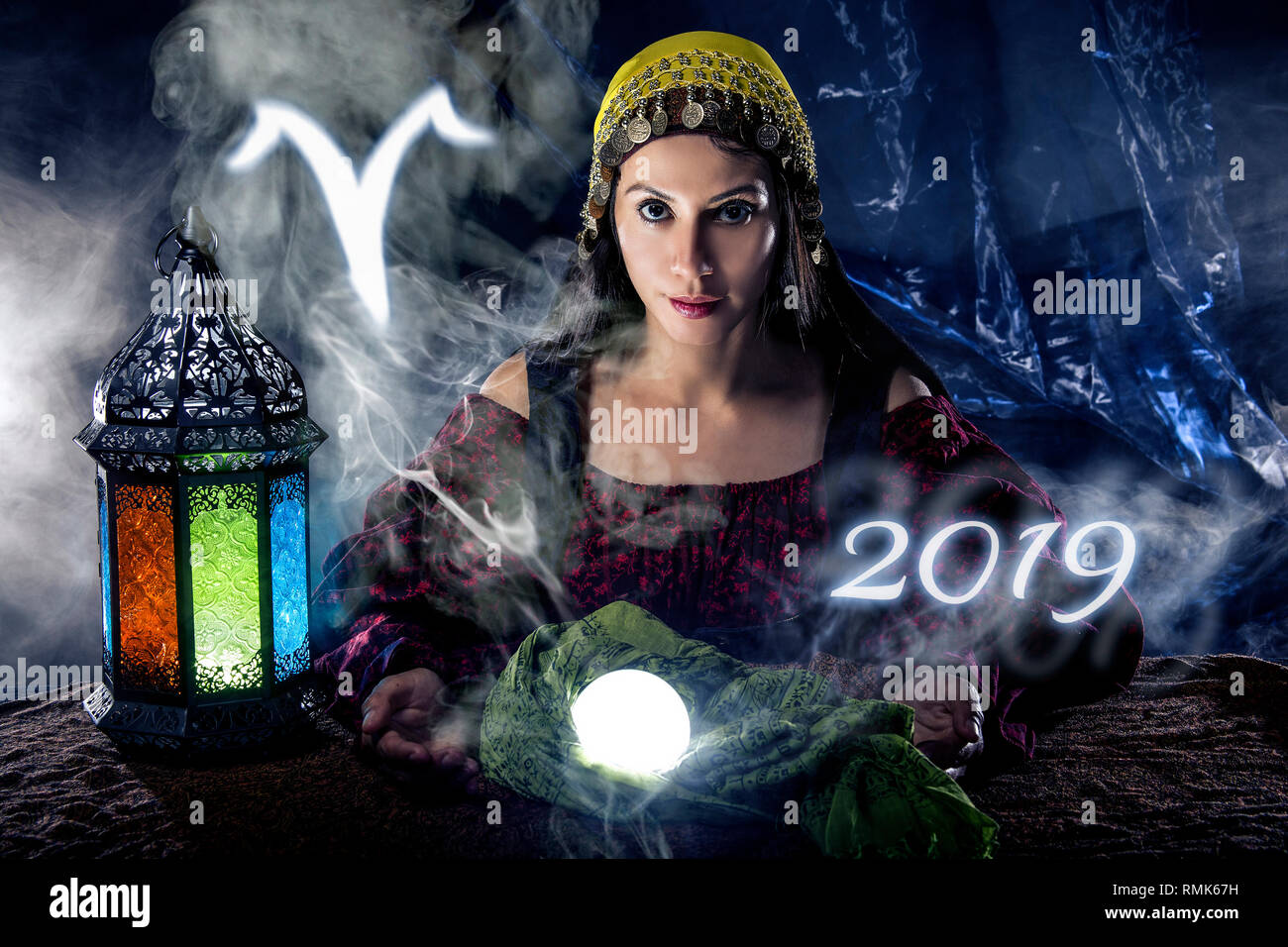 Psychic or fortune teller with crystal ball and horoscope zodiac sign of Aries - Stock Image