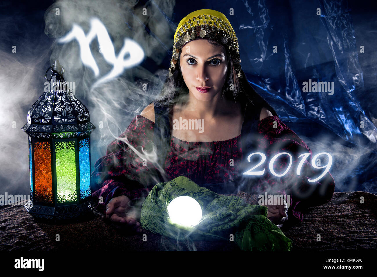 Psychic or fortune teller with crystal ball and horoscope zodiac sign of capricorn - Stock Image