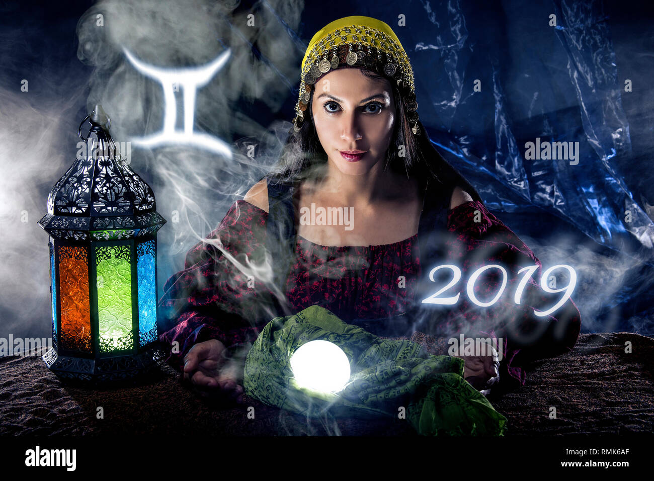 Psychic or fortune teller with crystal ball and horoscope zodiac sign of Gemini - Stock Image