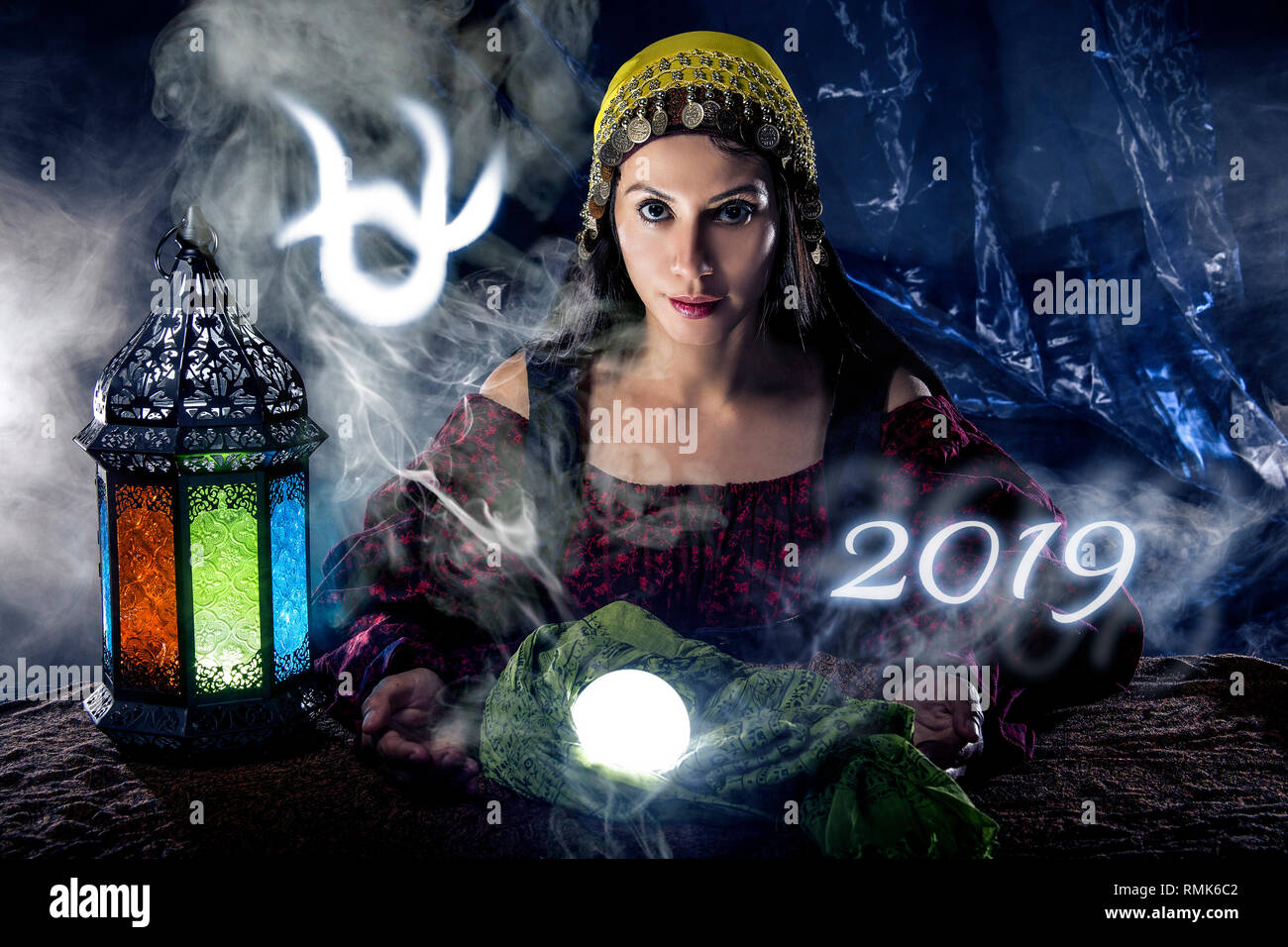 Psychic or fortune teller with crystal ball and horoscope zodiac sign of Ophiuchus - Stock Image