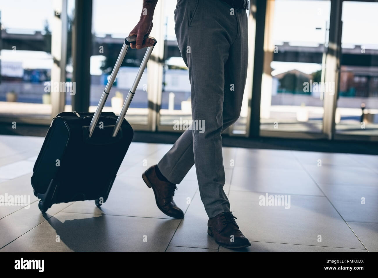 Businessman walking with his travel suitcase - Stock Image