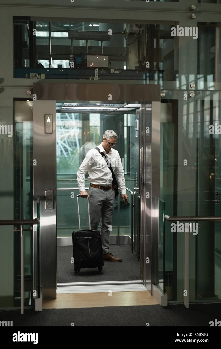 Businessman with travel suitcase in the elevator - Stock Image