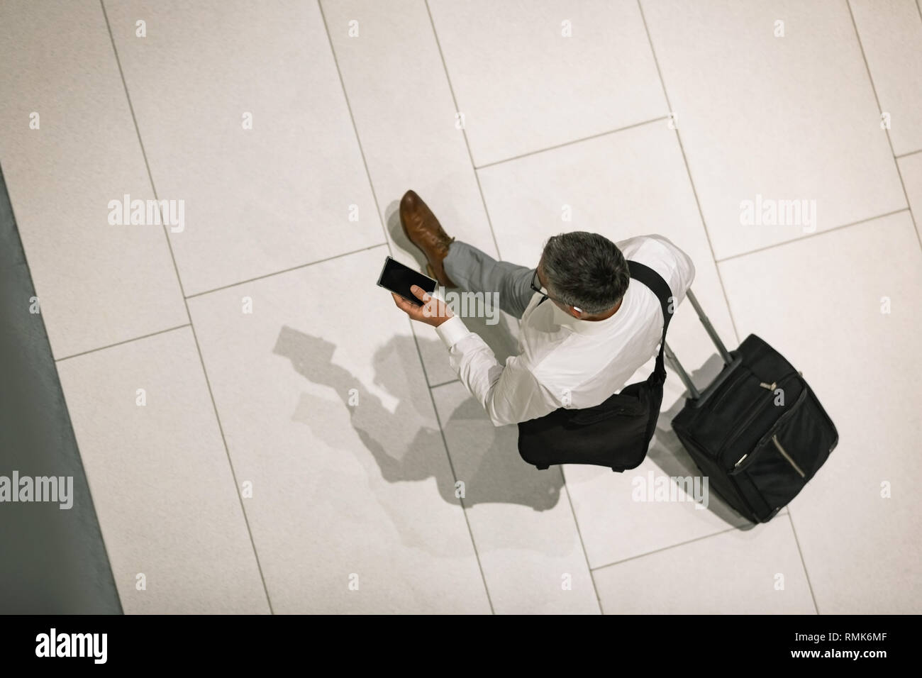 Businessman with travel suitcase and mobile phone walking - Stock Image