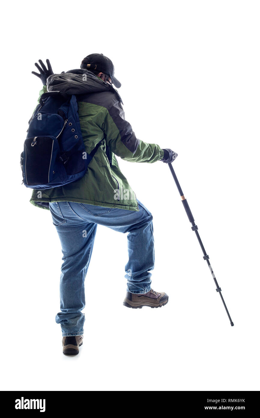Mountain Climber or Hiker poking something with a stick.  The man is isolated and acting like he is looking at something in his path - Stock Image