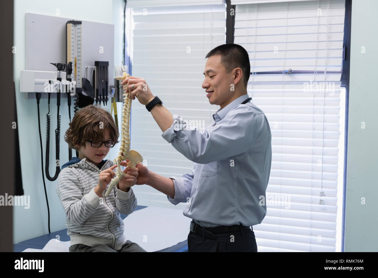 Young asian male doctor showing vertebral column model to caucasian boy patient - Stock Image