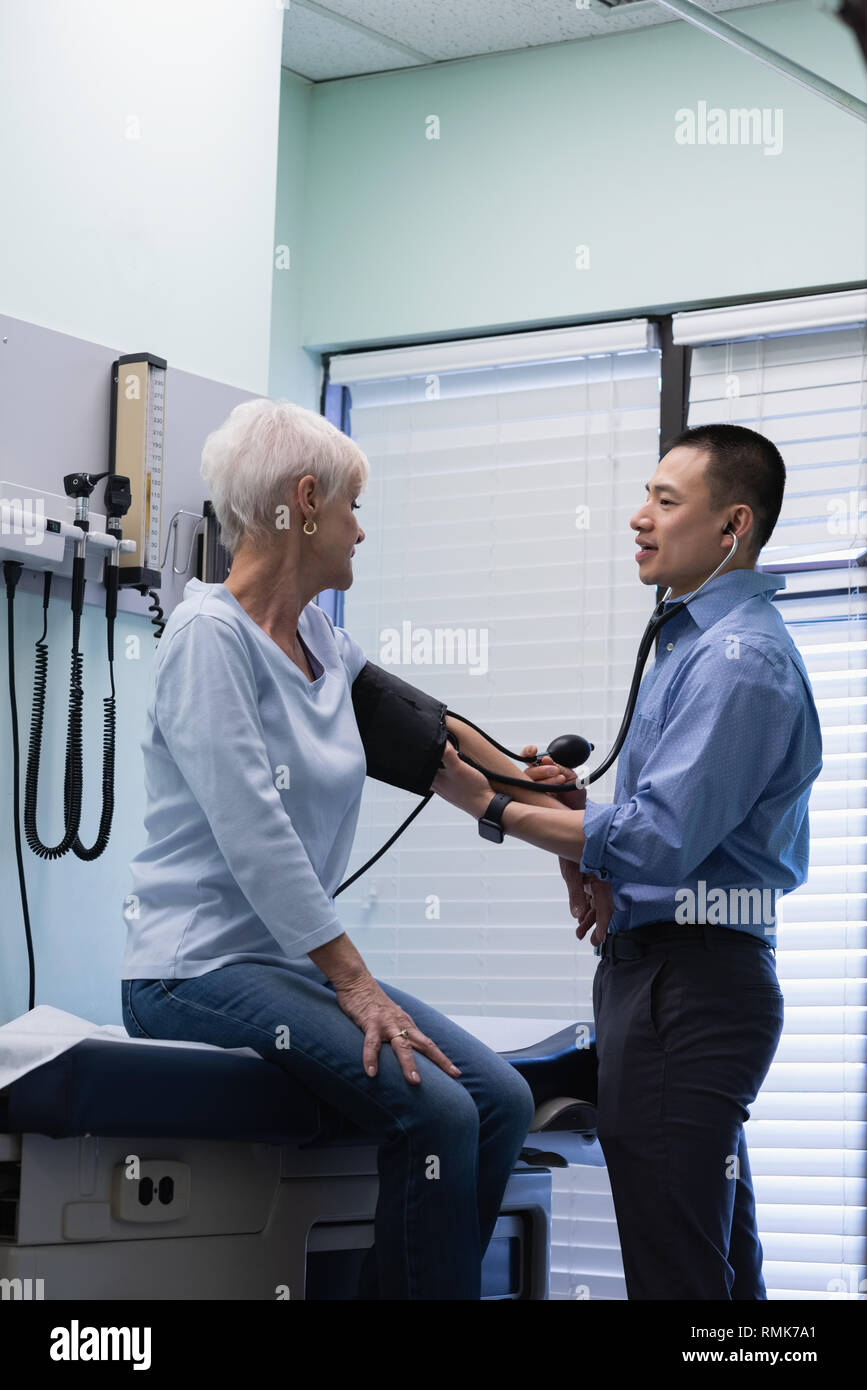 Male doctor checking blood pressure of senior patient blood pressure gauge at clinic - Stock Image