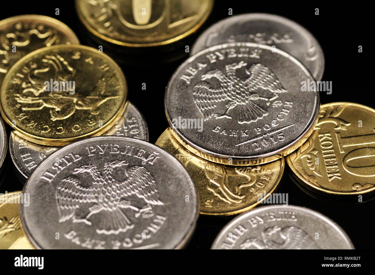 A macro image of an assortment of Russian Federation coins on a reflective black background - Stock Image
