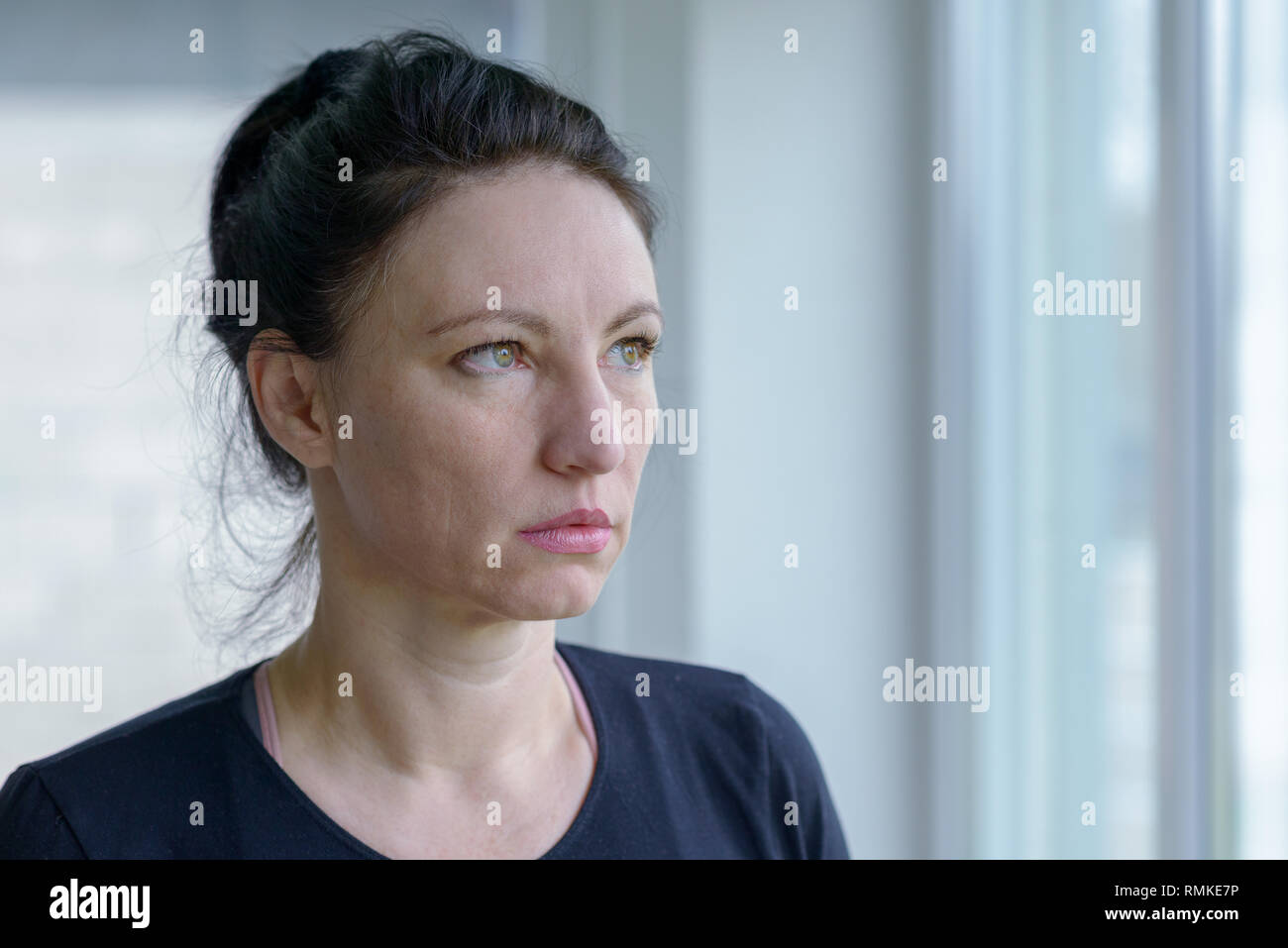 Thoughtful woman staring out of a window with a sombre deadpan expression in a head and shoulders portrait - Stock Image