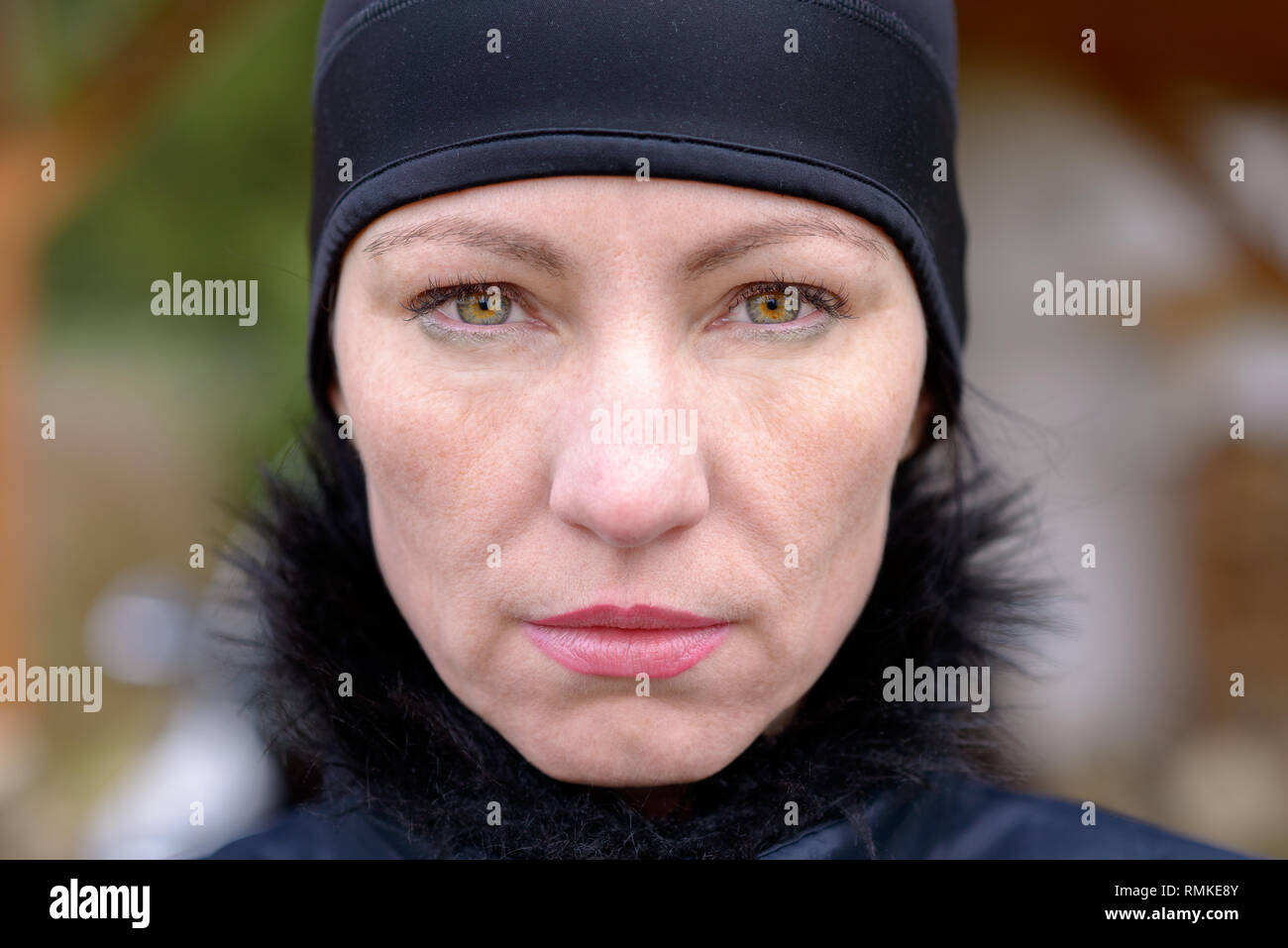 Attractive mature woman wearing a black winter hat staring at the camera with a penetrating look and deadpan expression - Stock Image