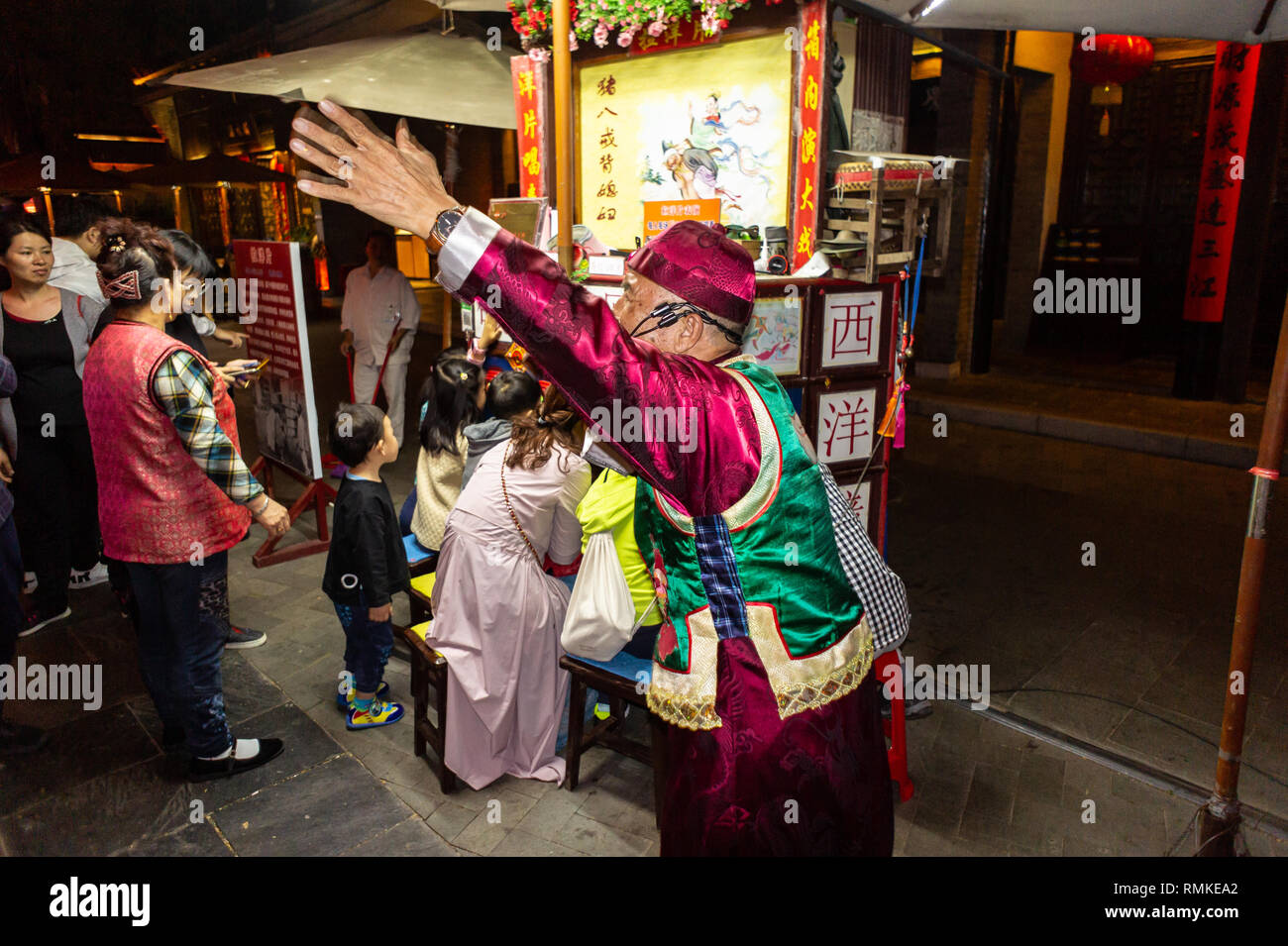 Chinese narrator gesticulates at a Peking peep show at a park in Shenzhen, China - Stock Image
