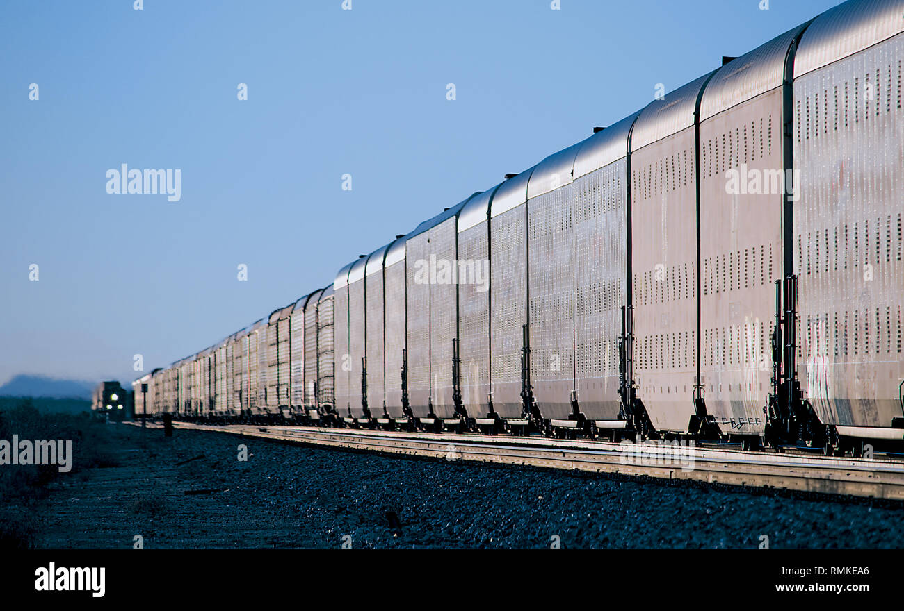 Automobile Train Meeting Doublestack Train in U.S. Desert - Stock Image