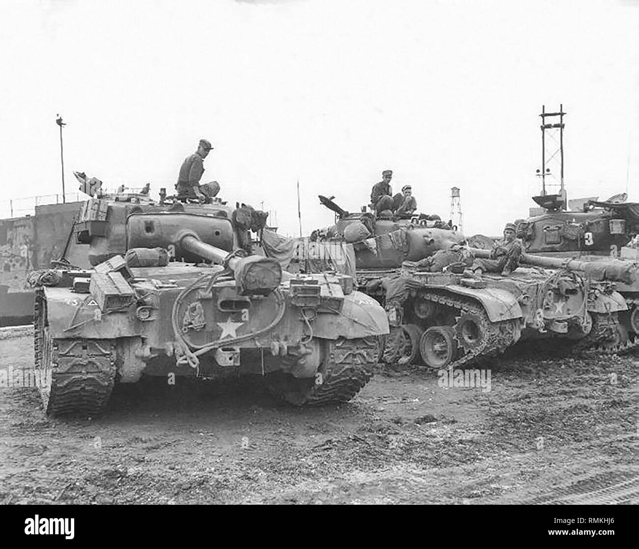Men and equipment of the 73rd Heavy Tank Battalion await orders to board the LST's at the Pusan Docks, Korea. - Stock Image