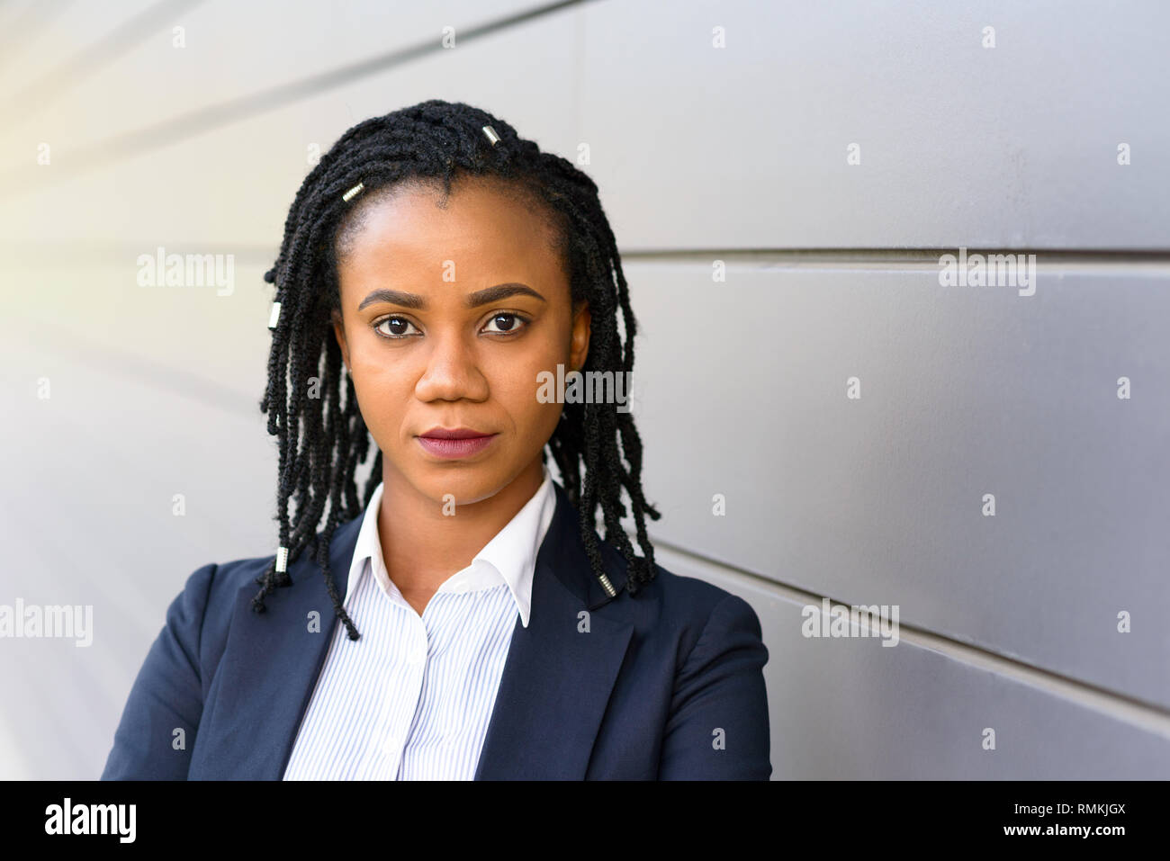 Outdoor portrait of serious elegant African American woman standing against wall - Stock Image