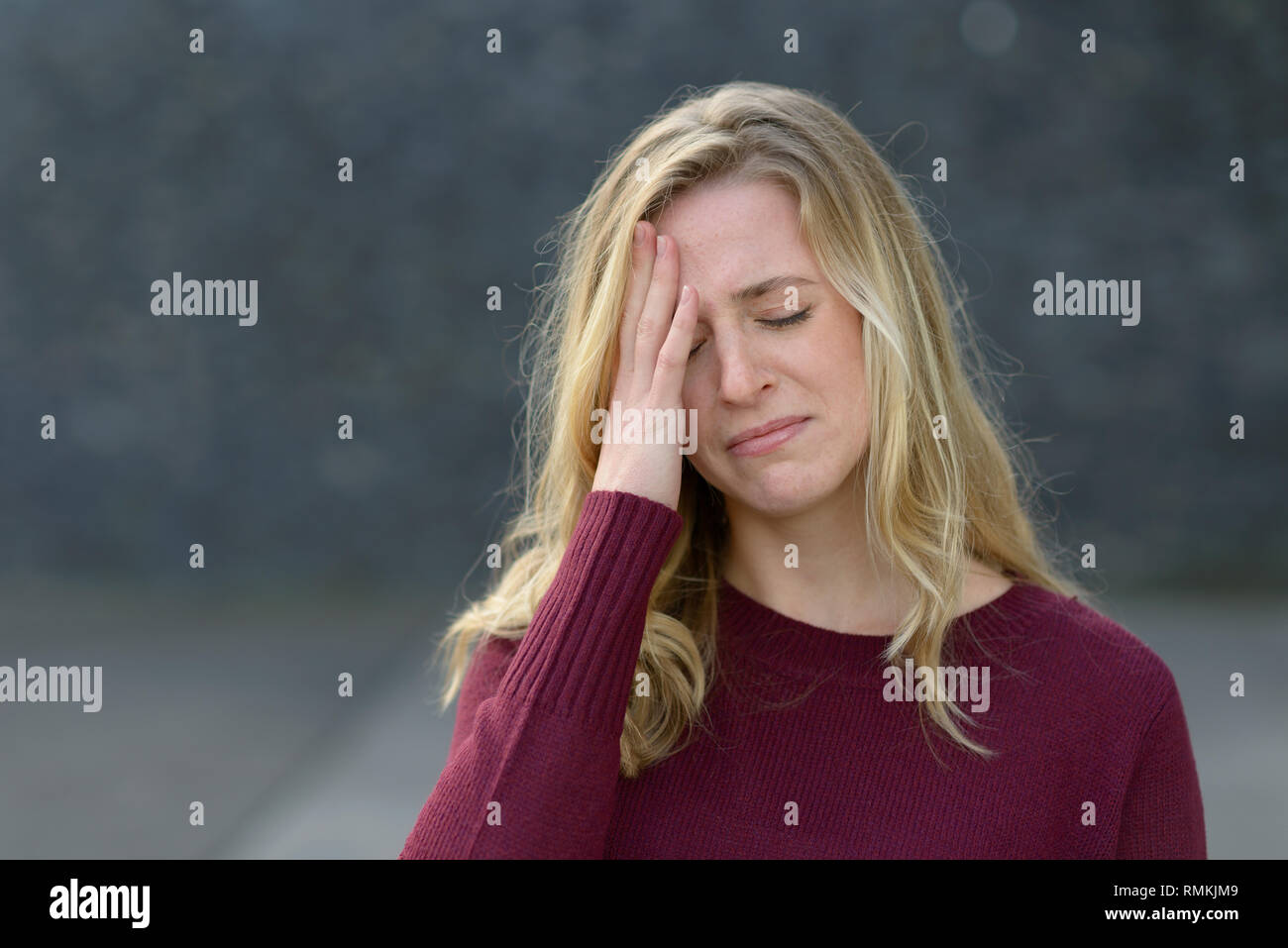 Upset young woman about to start crying holding her hand to her forehead with closed eyes and an anguished expression - Stock Image