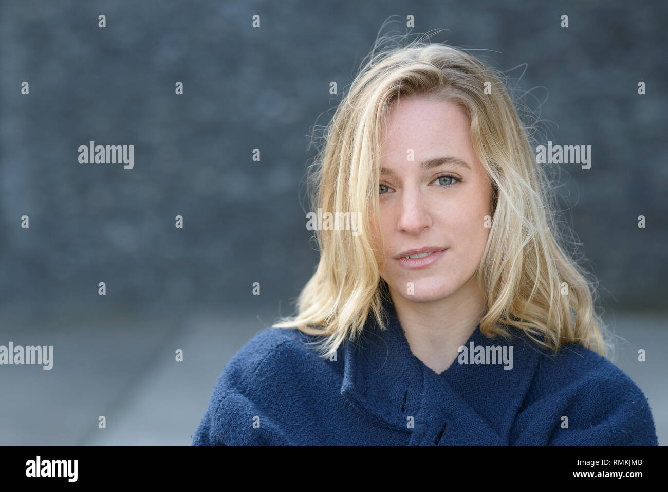 Attractive thoughtful young blond woman with tousled hair in fall or autumn standing outdoors looking pensively at the camera in a warm blue jacket - Stock Image