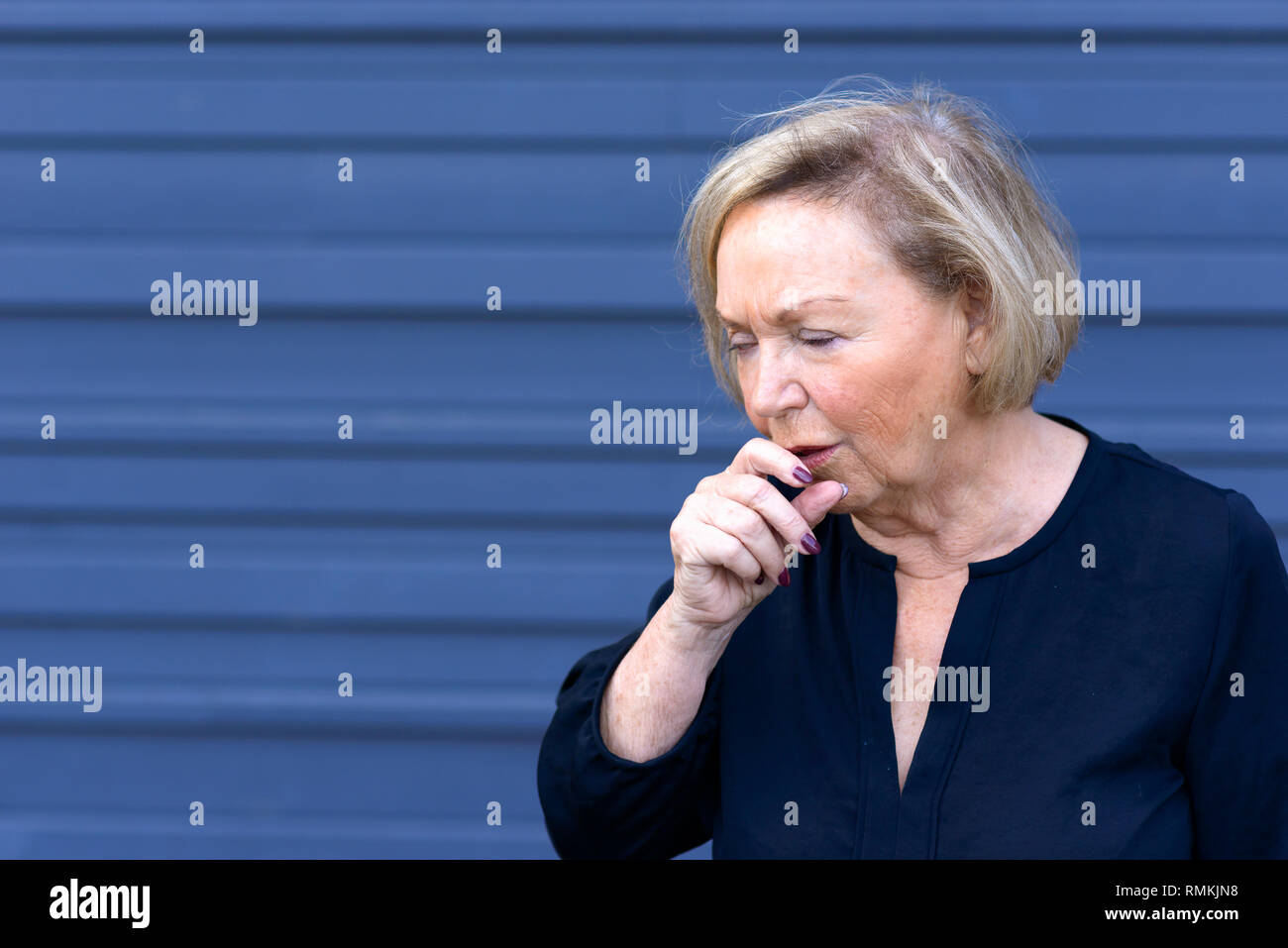Unwell elderly lady having a coughing fit holding her hand to her mouth conceptual of seasonal flu, allergies or choking over blue with copy space - Stock Image