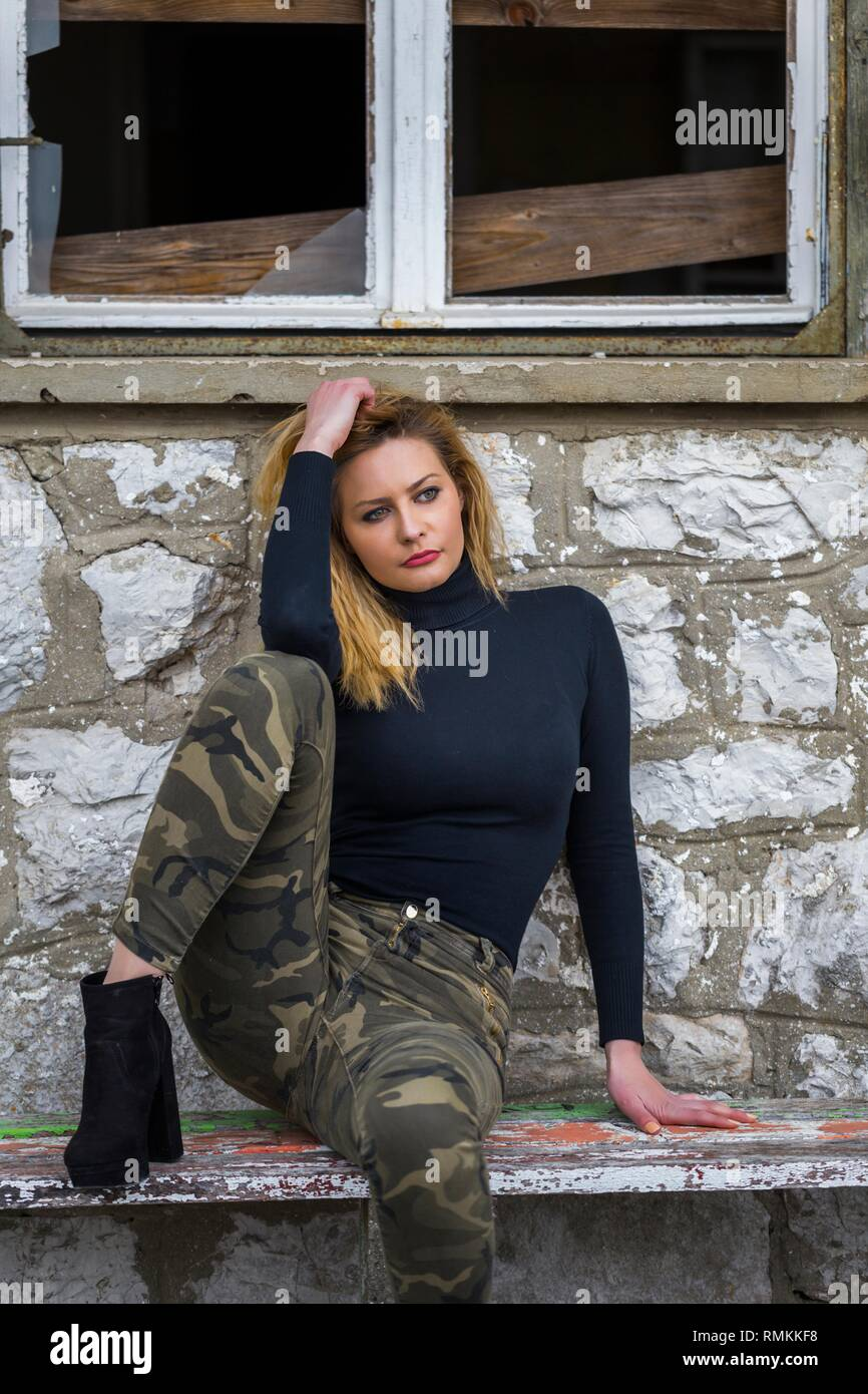 Young woman almost military clothing sitting under old rotten window frame derelict stone house - Stock Image