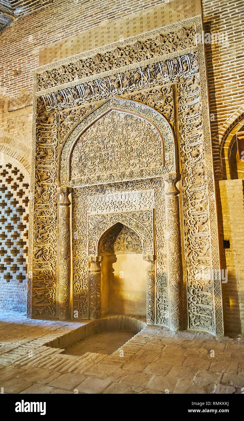 ISFAHAN, IRAN - OCTOBER 21, 2017: The carved stucco Uljayto mihrab is decorated with fine Islamic pattern, Quranc calligraphy and located in West pray Stock Photo