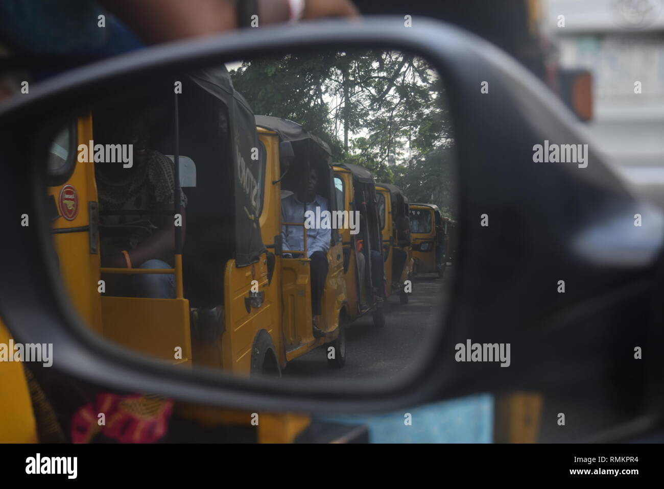photographs of tricycles a popular means of transportation taken from the reflection of the rear mirror of a car and in-front of the mirror in Lagos - Stock Image