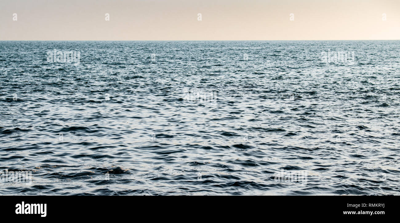 Beautiful photo of relatively calm sea surface (Arabian Sea) with clear horizon just after the sunset. Sunset giving a magical tint to the water color. - Stock Image