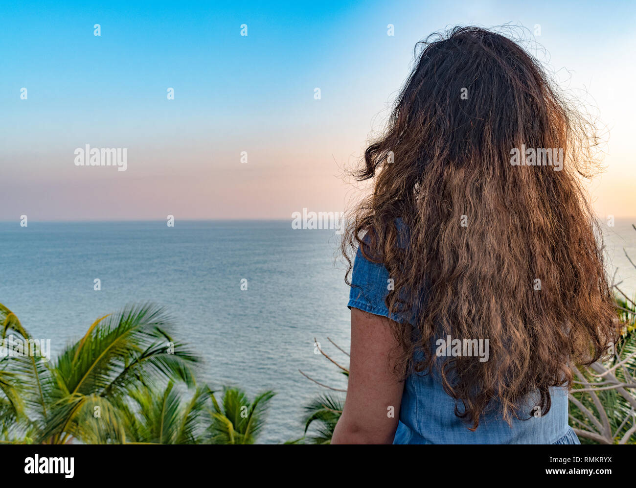Beautiful photo of a Brunette teenage girl with golden colored hair enjoying her dream vacation or solo trip to an exotic island. - Stock Image