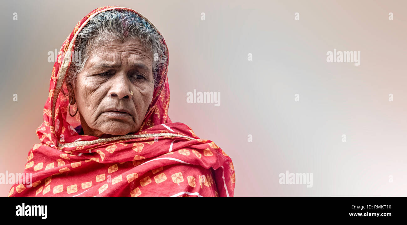 Beautiful photo of Old Aged Indian Woman farmer in her late 70s wearing red robe, in sad mood, because of poor harvest and losing her valuable assets Stock Photo