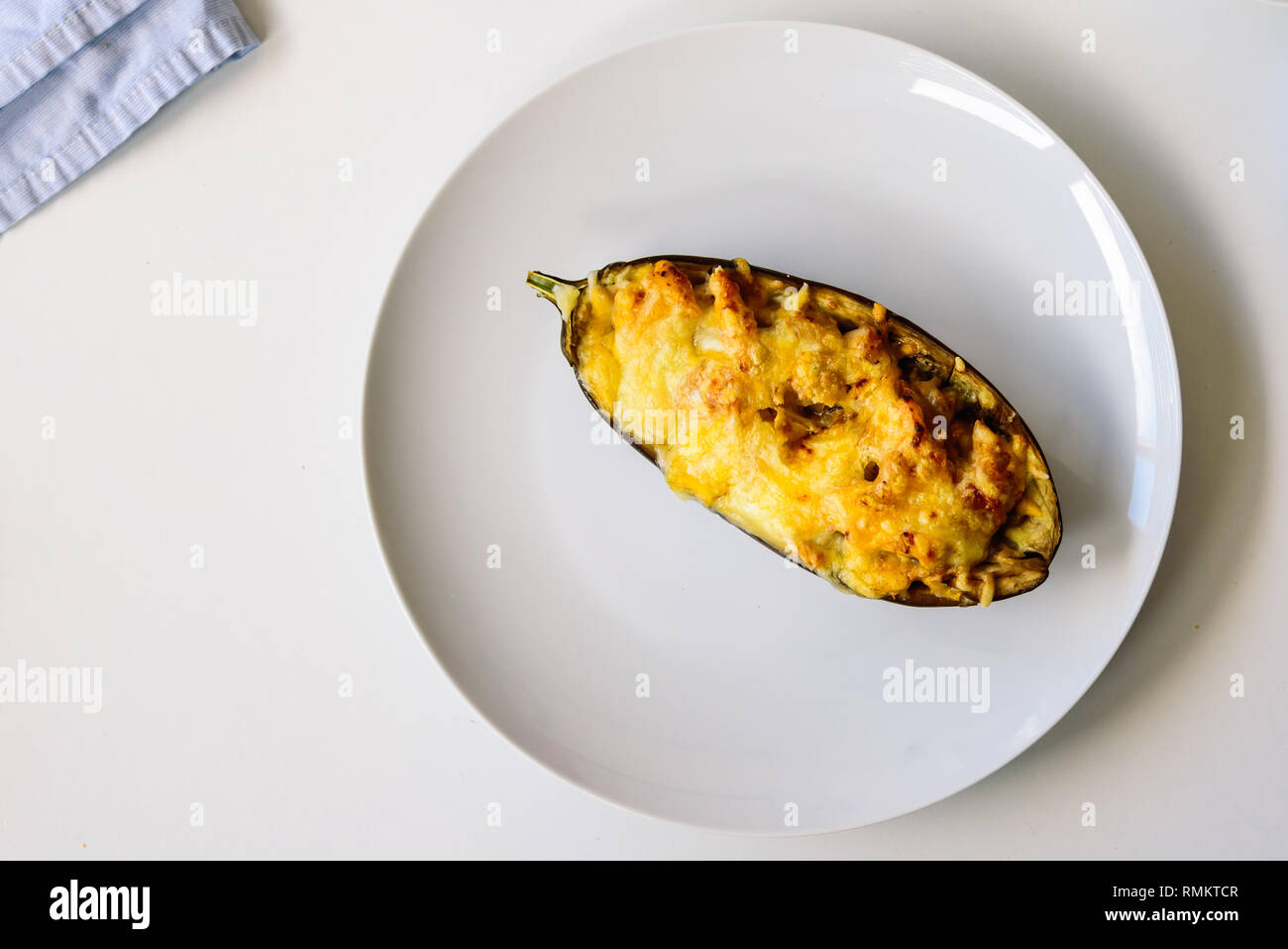 Half aubergine stuffed with meat with grated cheese in a white dish - Stock Image