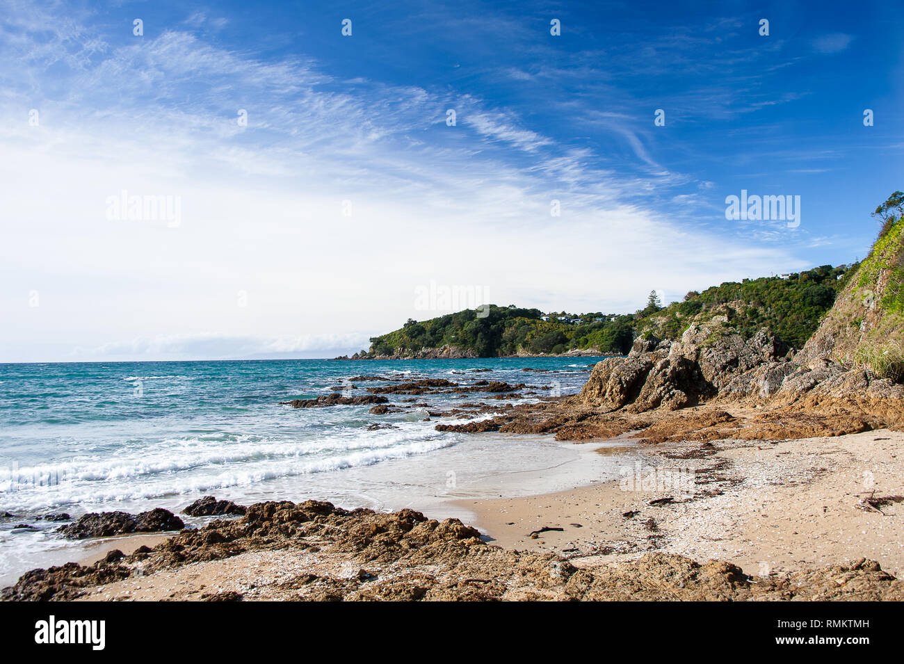 Waiheke Island, New Zealand. Picturesque bay on rugged coastline with rocky foreground and blue cloudy sky - Stock Image
