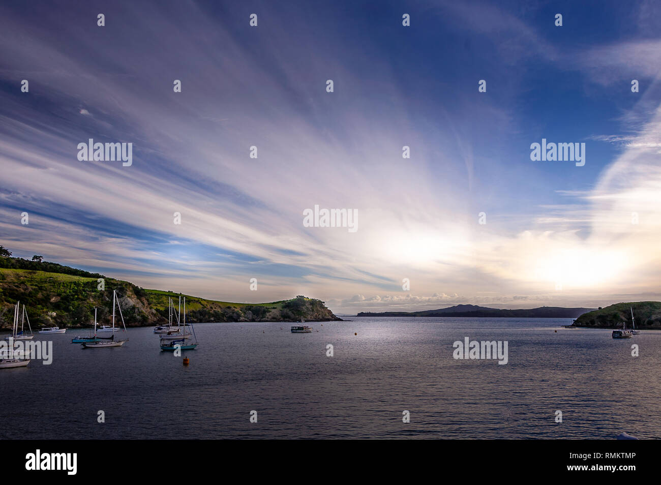 Dramatic sunset viewed from the Waiheke to Auckland inter-island ferry. Tranquil bay with sailing boats at anchor, against backlit clouds - Stock Image