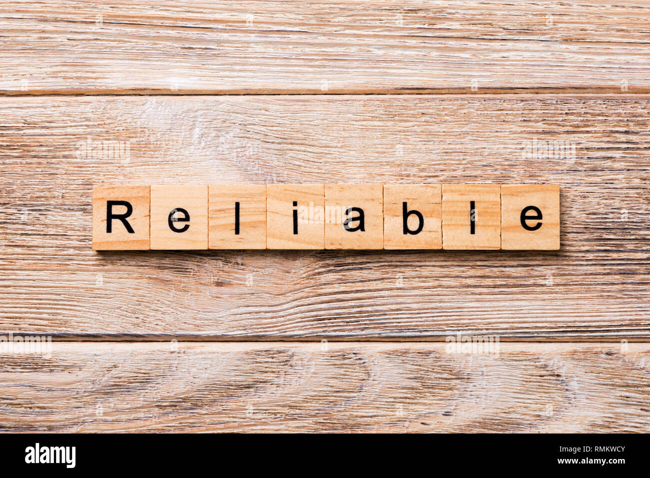 Reliable word written on wood block. Reliable text on wooden table for your desing, concept. - Stock Image