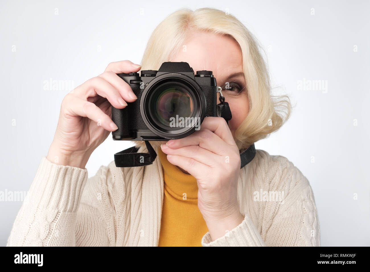 Senior blonde woman taking photo with camera - Stock Image