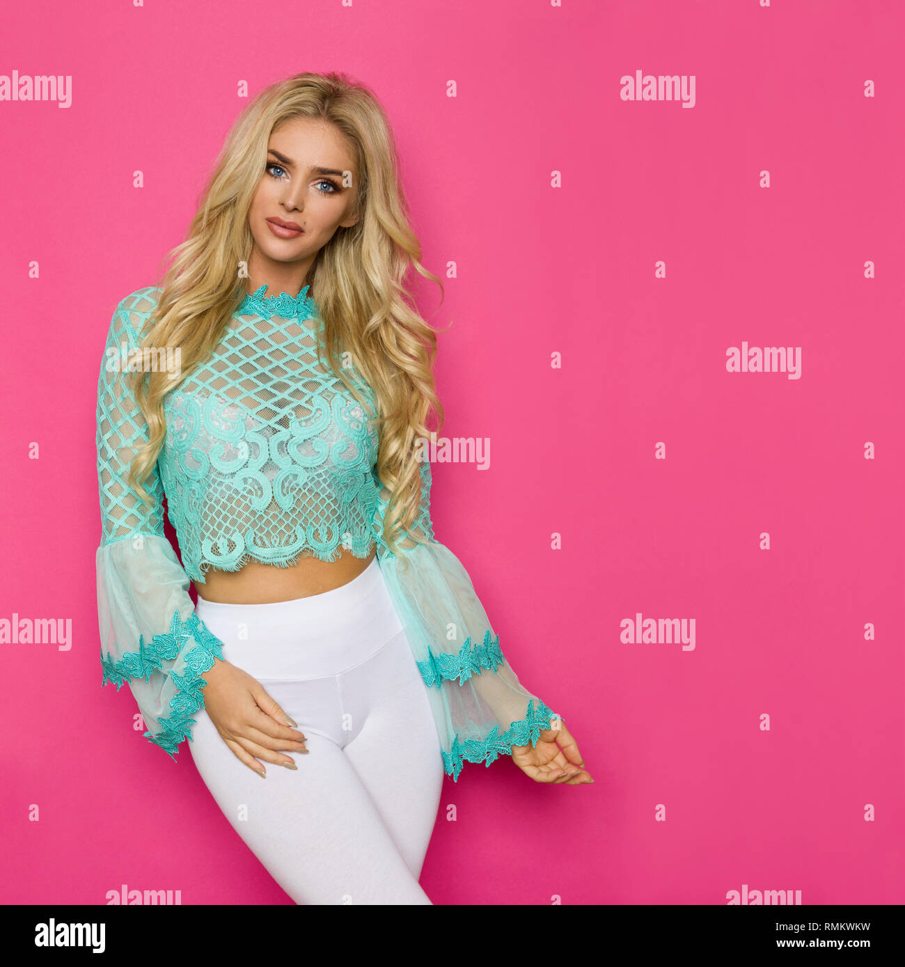 fd65825043c0b Beautiful blond woman in turquoise lace blouse and white leggings is posing  on pink background. Three quarter length studio shot.