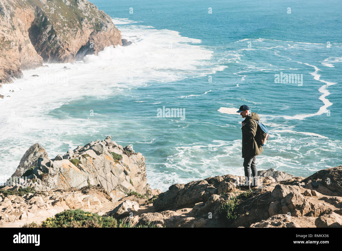 A man tourist with a backpack stands in solitude at Cape Roca in Portugal. - Stock Image