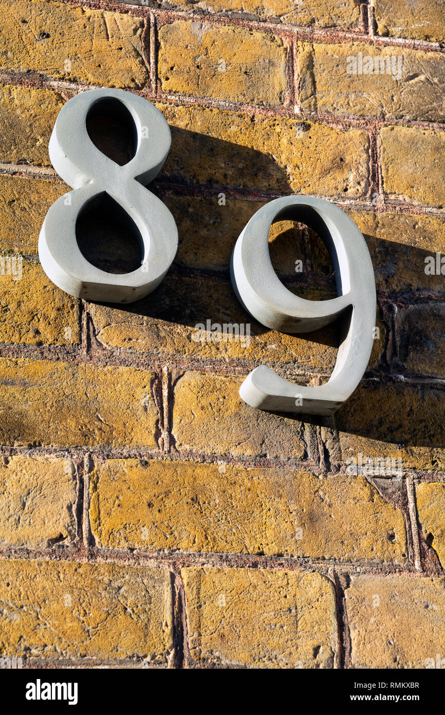 Number eighty nine on exterior wall in strong sunshine - Stock Image