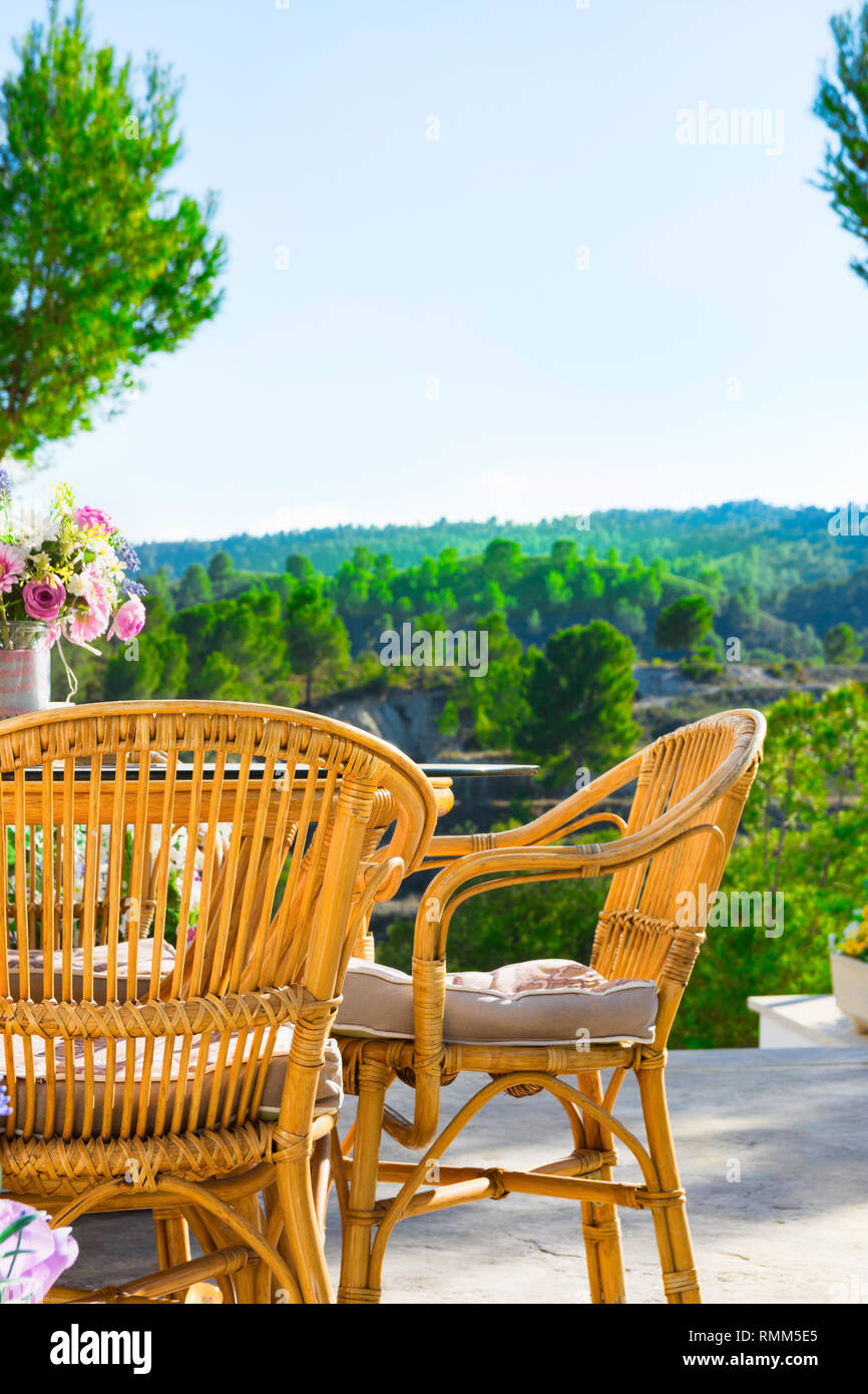Terrace of luxurious white villa with wicker chairs table flowers bouquet on table fascinating view of valley mountains covered with green trees. Sunn Stock Photo