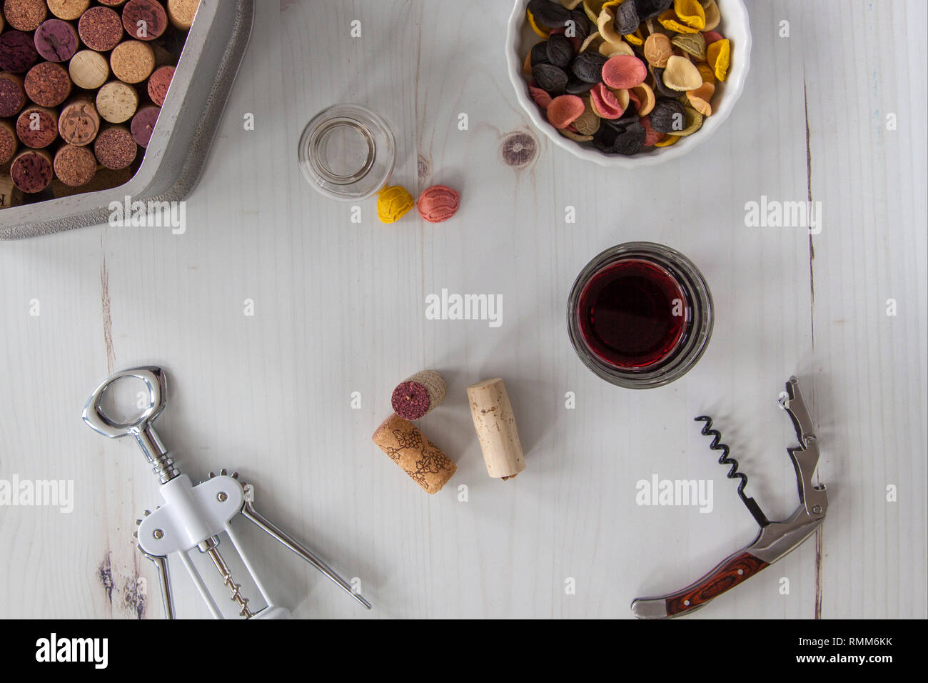 Corkscrews with corks, wine and pasta, overhead - Stock Image