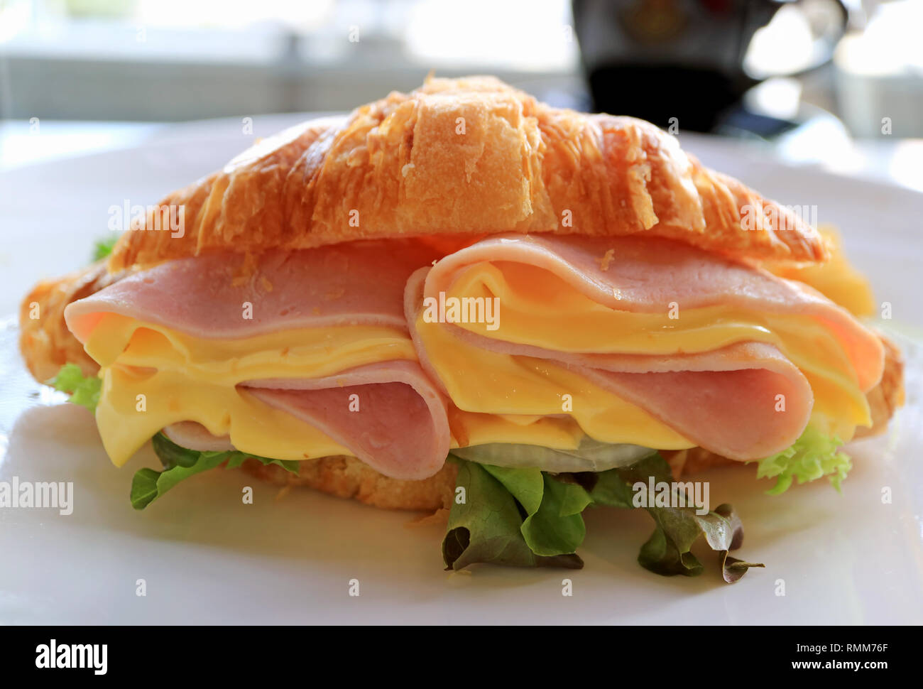 Delectable ham and cheese with fresh lettuce croissant sandwich - Stock Image