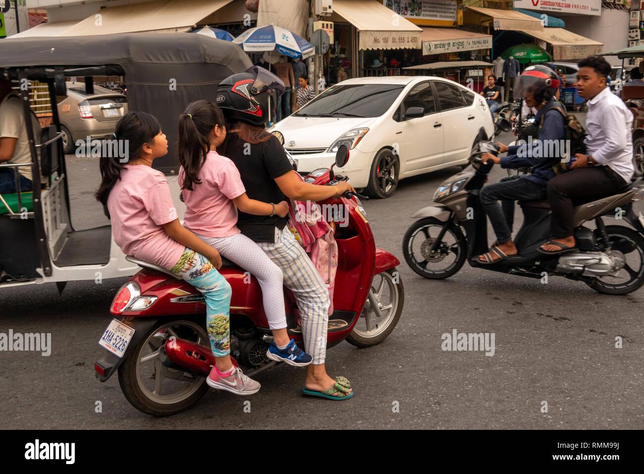 Cambodia, Phnom Penh, Chamkar Mon District, Russian Market, Phsar, Tuol Tom Poung, traffic chaos, at road junction, three people on motorbike - Stock Image