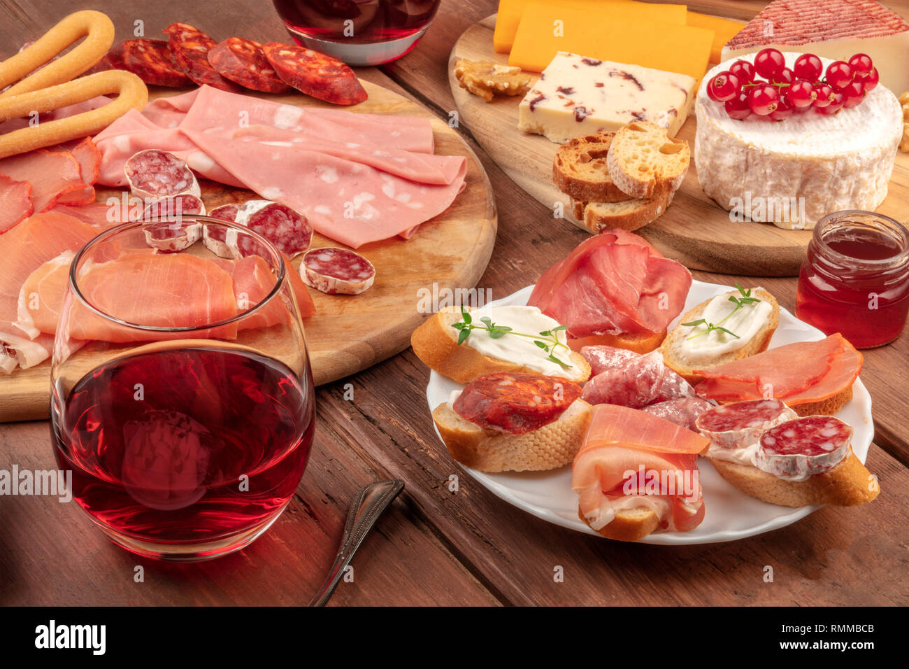Wine tasting and pairing. A wineglass with charcuterie, sandwiches and a cheese platter on a dark wooden background - Stock Image