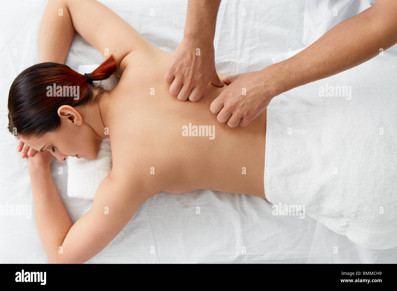 Young beautiful woman enjoying a back massage. Professional massage therapist is treating a female patient in apartment. Relaxation, beauty, body and  Stock Photo