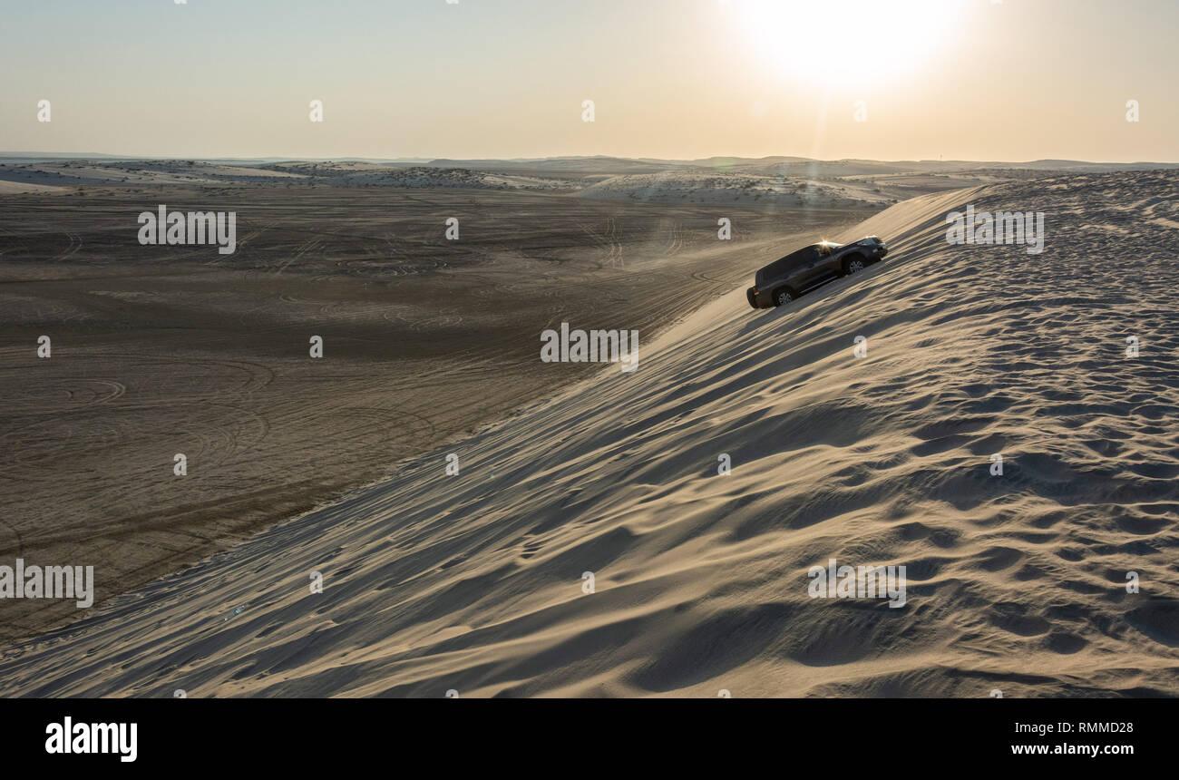 Khor Al Adaid, Qatar - November 5, 2016. 4WD vehicle driving up a sand dune in Khor Al Adaid desert in Qatar. - Stock Image