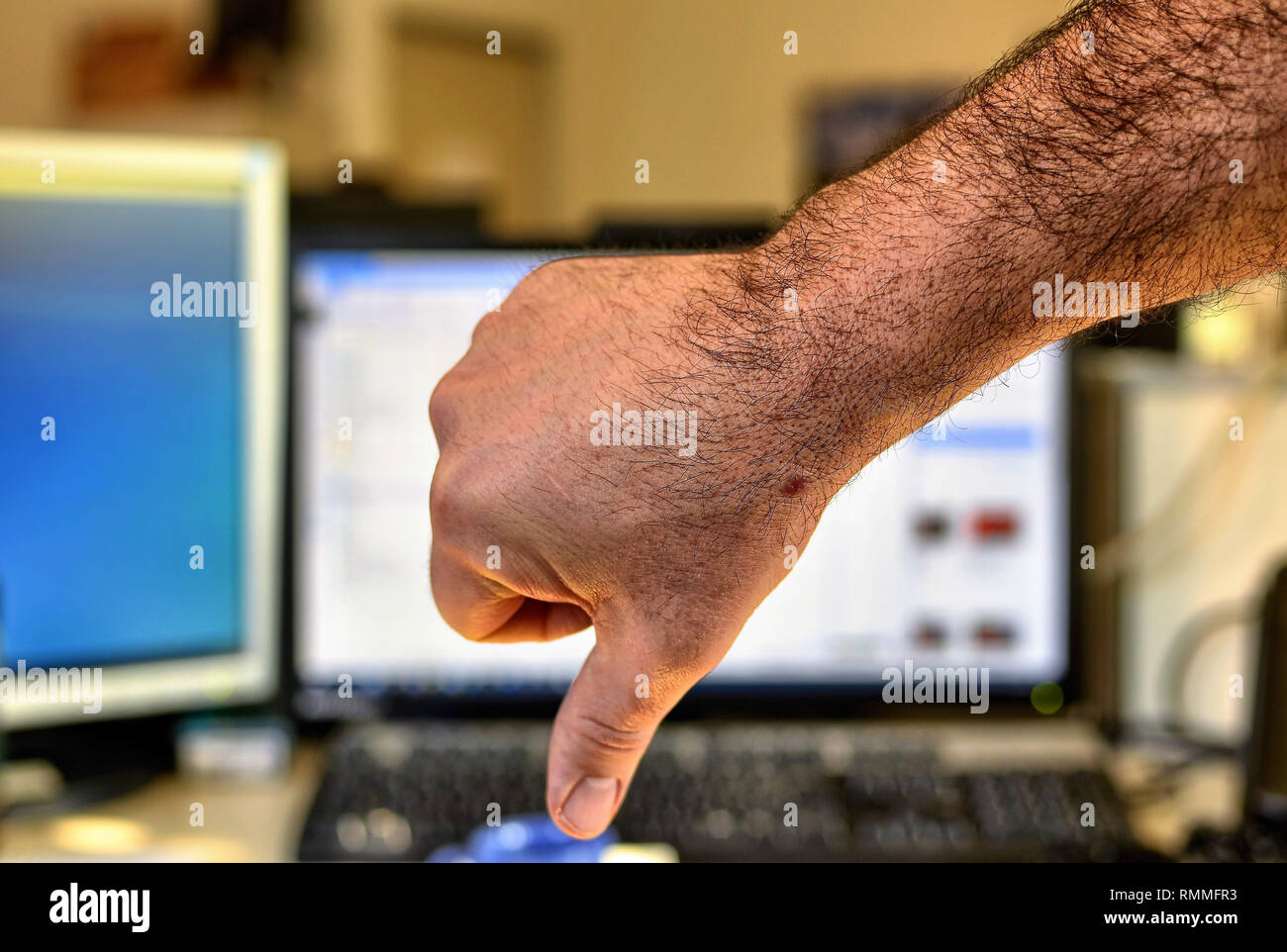 Male hand of Caucasian man makes thumbs down gesture. Indistinguishable blurred background of an office. - Stock Image