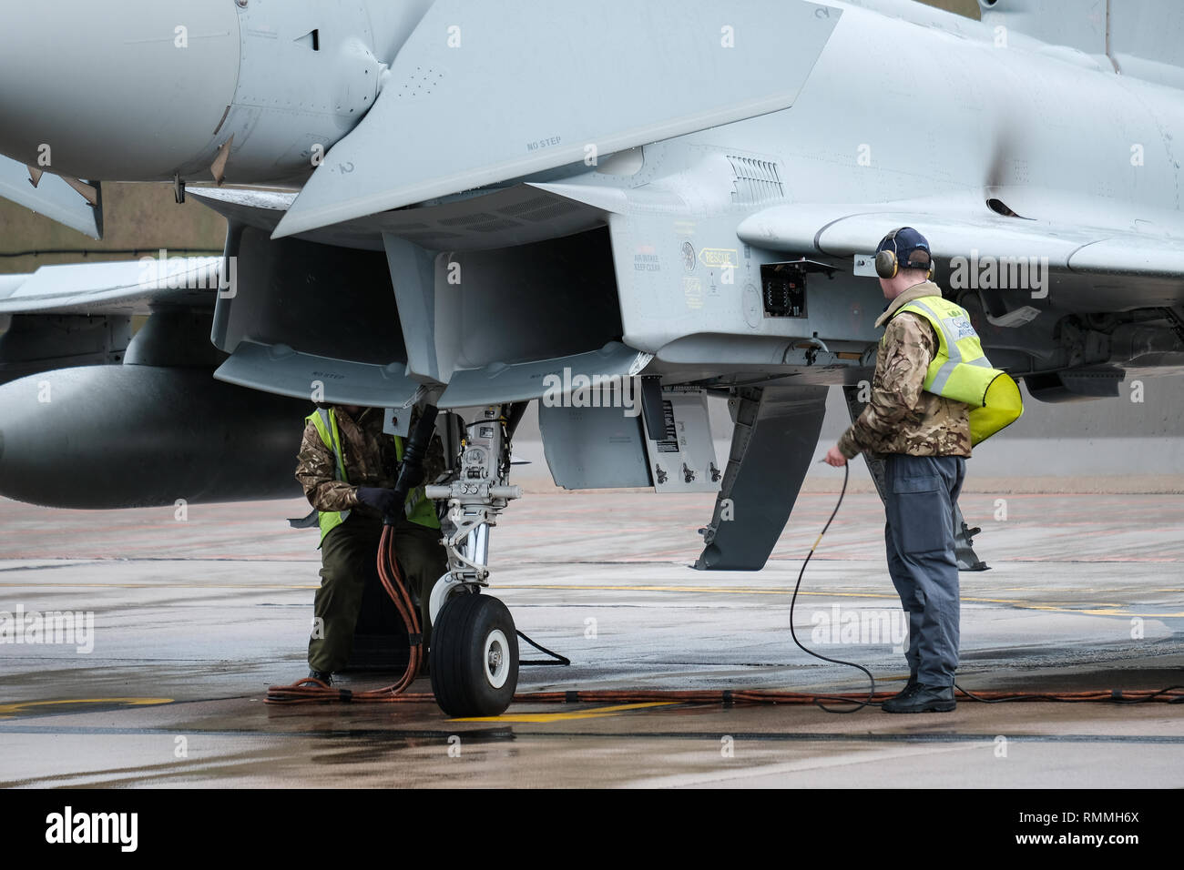 Ground crew conducting a pre-flight check over an RAF Tornado jet fighter at RAF Lossiemouth base, Moray, Scotland - Stock Image