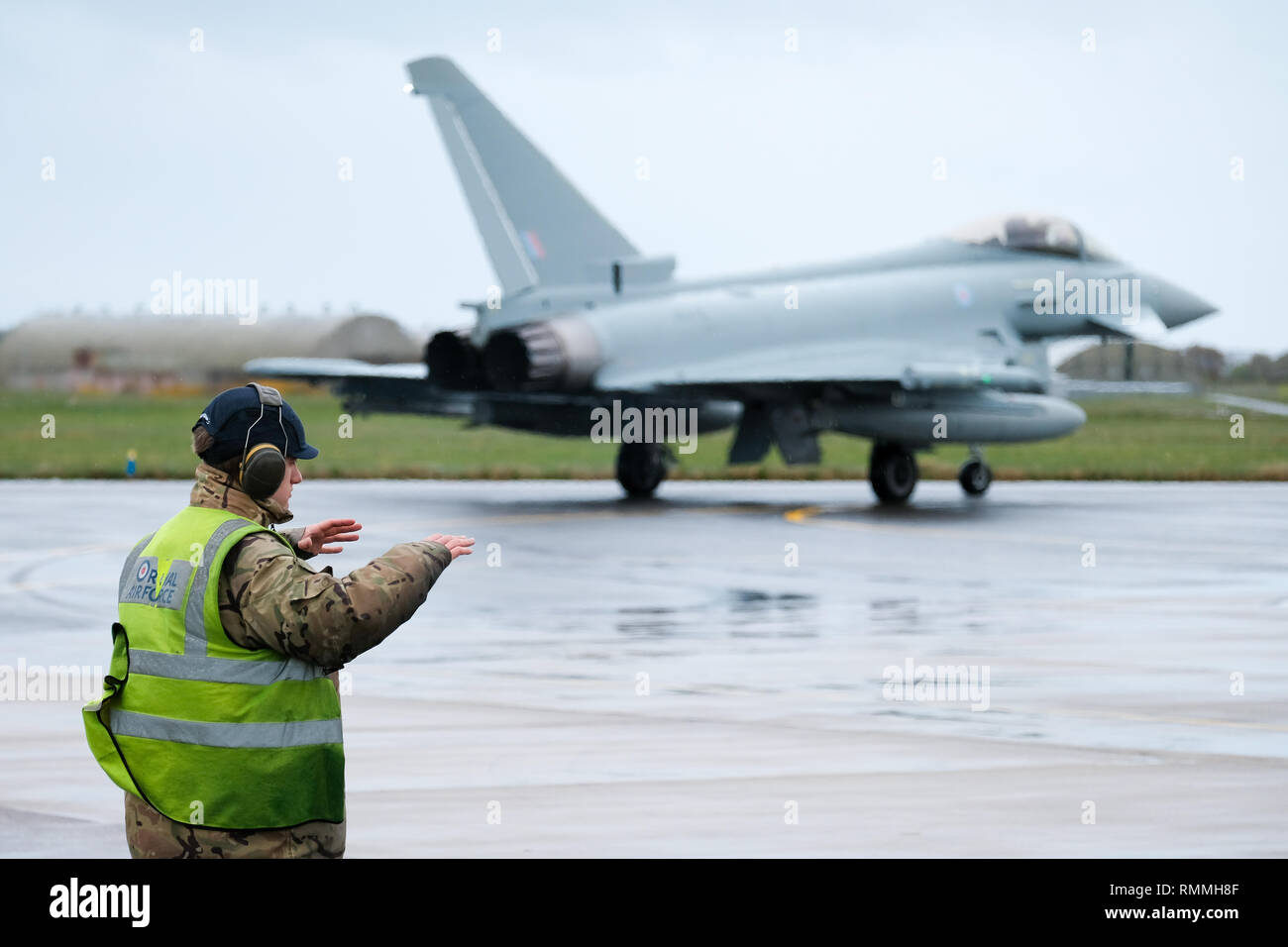 Ground crew signal an RAF Tornado jet fighter for take-off at RAF Lossiemouth base, Moray, Scotland - Stock Image